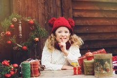 Gelukkig kindmeisje in rode hoed en sjaal verpakkende Kerstmisgiften bij comfortabel buitenhuis, dat voor Nieuwjaar en Kerstmis w royalty-vrije stock foto