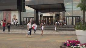 Gelukkig kopers uit gekomen stadswinkelcentrum, mensen die langs stedelijke straat lopen stock videobeelden