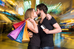 Gelukkig kussend paar met het winkelen zakken Royalty-vrije Stock Afbeeldingen