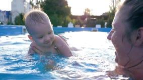 Gelukkig lachen weinig jongen en zijn moeder en hebben pret in zwembad met blauw water stock video