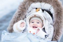 Gelukkig lachend babymeisje in warme wandelwagen Royalty-vrije Stock Foto's