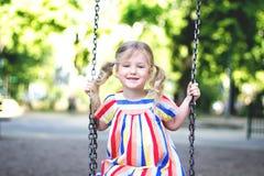 Gelukkig lachend kindmeisje op schommeling stock foto