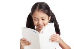Gelukkig las weinig Aziatisch meisje een boek Stock Fotografie