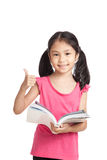Gelukkig las weinig Aziatisch meisje een boek duimen toont Stock Afbeelding