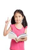 Gelukkig las weinig Aziatisch meisje een boek overwinningsteken toont Stock Foto's