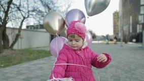 Gelukkig leuk kind bij de straat met ballons met helium De partij van de verjaardag stock video