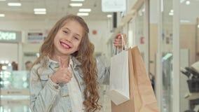 Gelukkig leuk meisje die duimen tonen bij het winkelcomplex stock videobeelden