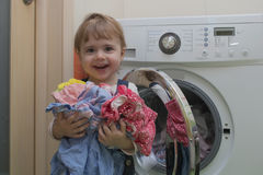 Gelukkig leuk meisje met kleren die wasserij in huisbinnenland doen stock foto's