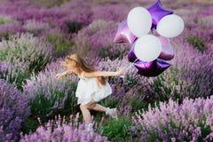 Gelukkig leuk meisje op lavendelgebied met purpere ballons Het concept van de vrijheid stock afbeelding