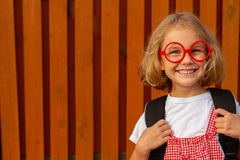 Gelukkig leuk slim meisje in glazen met schooltas royalty-vrije stock foto