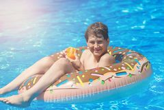 Gelukkig leuk weinig jongenstiener die op opblaasbare doughnutring met sinaasappel in zwembad liggen Actieve spelen op water, vak royalty-vrije stock foto's