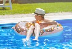 Gelukkig leuk weinig jongenstiener die op opblaasbare doughnutring met sinaasappel in zwembad liggen Actieve spelen op water, vak stock afbeelding