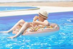 Gelukkig leuk weinig jongenstiener die op opblaasbare doughnutring met sinaasappel in zwembad liggen Actieve spelen op water, vak stock afbeeldingen