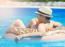 Gelukkig leuk weinig jongenstiener die op opblaasbare doughnutring met sinaasappel in zwembad liggen Actieve spelen op water, vak royalty-vrije stock fotografie