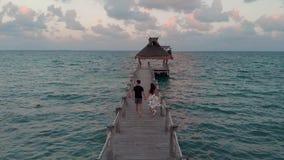 Gelukkig in liefdepaar die onderaan een houten dok buiten een beachfronttoevlucht dichtbij Cancun, Mexico bij zonsondergang lopen stock footage