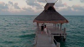 Gelukkig in liefdepaar die onderaan een houten dok buiten een beachfronttoevlucht dichtbij Cancun, Mexico bij zonsondergang lopen stock video