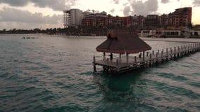 Gelukkig in liefdepaar die op het eind van een houten dok buiten een beachfronttoevlucht dichtbij Cancun, Mexico bij zonsondergan stock video