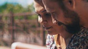 Gelukkig in liefdepaar die smartphonezitting op bank gebruiken De zomer winderige dag stock footage
