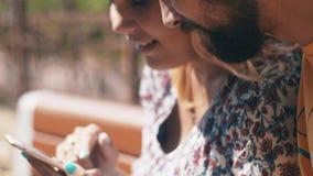 Gelukkig in liefdepaar die smartphonezitting op bank gebruiken De zonnige dag van de zomer stock video