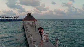 Gelukkig in liefdepaar het kussen buiten een beachfronttoevlucht dichtbij Cancun, Mexico bij zonsondergang stock videobeelden