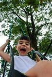 Gelukkig Little Boy dat op Schommeling glimlacht stock foto