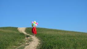 Gelukkig lopend meisje in de groene weiden met kleurrijke ballons stock footage
