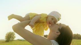 Gelukkig mamma die haar glimlachend babymeisje houden tegen glanzende zon stock video