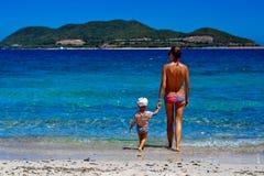 Gelukkig mamma en haar aanbiddelijke kleine dochter tijdens de zomervakantie op het strand Stock Afbeelding