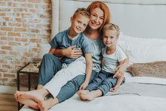 Gelukkig mamma en twee jonge geitjes die in bed ontspannen stock afbeeldingen