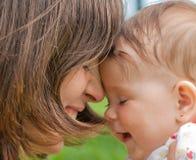 Gelukkig mamma met een meisje dat op het gras speelt Stock Foto's