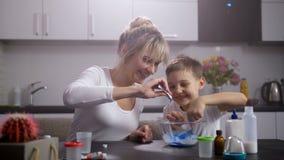 Gelukkig mamma met zoon die slijm in huiskeuken maken stock videobeelden