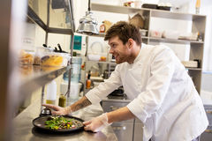 Gelukkig mannelijk chef-kok kokend voedsel bij restaurantkeuken Royalty-vrije Stock Afbeeldingen
