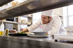 Gelukkig mannelijk chef-kok kokend voedsel bij restaurantkeuken Stock Foto's