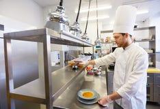 Gelukkig mannelijk chef-kok kokend voedsel bij restaurantkeuken Royalty-vrije Stock Foto's