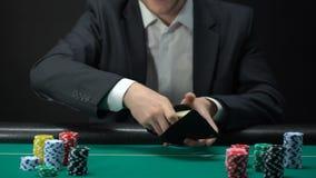 Gelukkig mannetje die dollarrekeningen in portefeuille, potprijs, spelfortuin, het gokken zetten stock footage