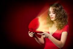 Gelukkig meisje dat een gift op de Dag van de Valentijnskaart \ 'opent s Stock Afbeelding