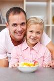 Gelukkig meisje dat fruit met haar vader eet Royalty-vrije Stock Afbeeldingen