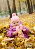 Gelukkig meisje in de bladeren Royalty-vrije Stock Foto
