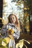 Gelukkig meisje in de bladerenherfst Stock Foto