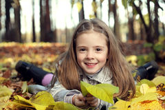 Gelukkig meisje in de bladerenherfst stock foto's