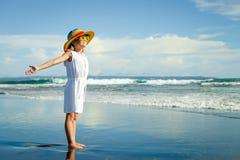 Gelukkig meisje in de hoed die zich bij het strand in de dag t bevinden royalty-vrije stock foto's