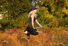 Gelukkig meisje in de vliegen van het heksenkostuum op bezemsteel Royalty-vrije Stock Fotografie