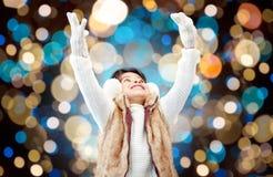 Gelukkig meisje in de winteroorbeschermers over vakantielichten Stock Foto