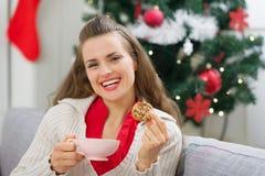 Gelukkig meisje dichtbij Kerstboom met kop en koekje royalty-vrije stock afbeelding