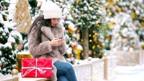 Gelukkig meisje dichtbij sparrentak in sneeuw voor nieuw jaar stock footage