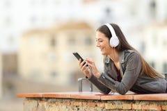 Gelukkig meisje die aan muziek van telefoon in een balkon luisteren stock foto's