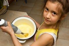 Gelukkig meisje die deeg voor een verjaardagscake mengen, die onafhankelijk en trots, helpend mum in de keuken zijn Onafhankelijk royalty-vrije stock fotografie