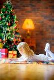 Gelukkig meisje die een brievensanta schrijven die op de vloer liggen stock afbeelding