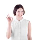 Gelukkig meisje die een O.K. teken maken Een glimlachende vrouw in een licht die overhemd op een witte achtergrond wordt geïsolee stock foto's