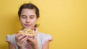 Gelukkig meisje die een plak van pizzaconcept eten hongerige tiener het kind eet een plak van pizza langzame motielevensstijl stock footage